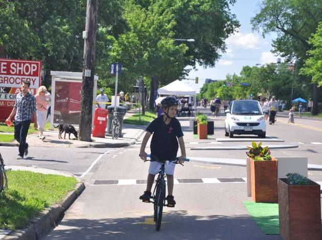 Bikes help us imagine a better city. At Open Streets Lyndale June 7, this boy and many other people got to try out the pop-up protected bike lane Credit: