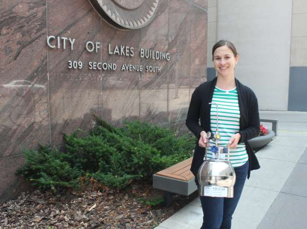 Jenni Lansing, a city environmental inspector, stands with an air monitoring canister. She has been tracking air quality with the canisters at several locations throughout the city.  Credit: Photo by Sarah McKenzie