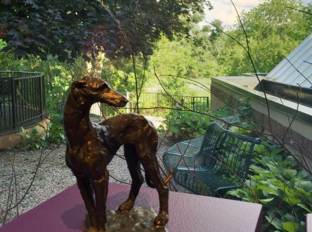 Longing to visit the nearby park, this bronze dog gazes out the gallery window. Credit: Photo by Linda Koutsky