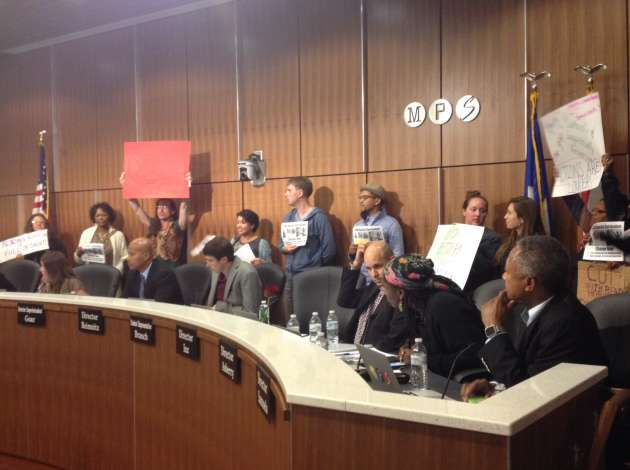 Protesters stood behind school board members as they attempted to vote on the district's proposed 2016 property tax levy. Credit: Dylan Thomas