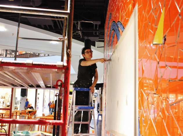 Credit: Artist Stacia Goodman installs a new mural and community bulletin board at Calhoun Square. Photo by Michelle Bruch