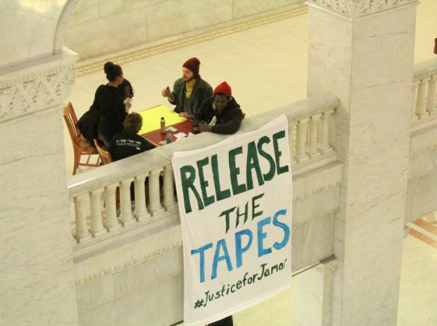 Protestors hung a banner in the City Hall rotunda Tuesday. Credit: Dylan Thomas