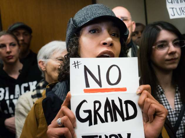 "Michaela Day stands with other demonstrators in County Attorney Mike Freeman's office Feb. 12, holding a sign that says ""#No Grand Jury"" in the Jamar Clark shooting case.  Credit: Photo by Annabelle Marcovici"