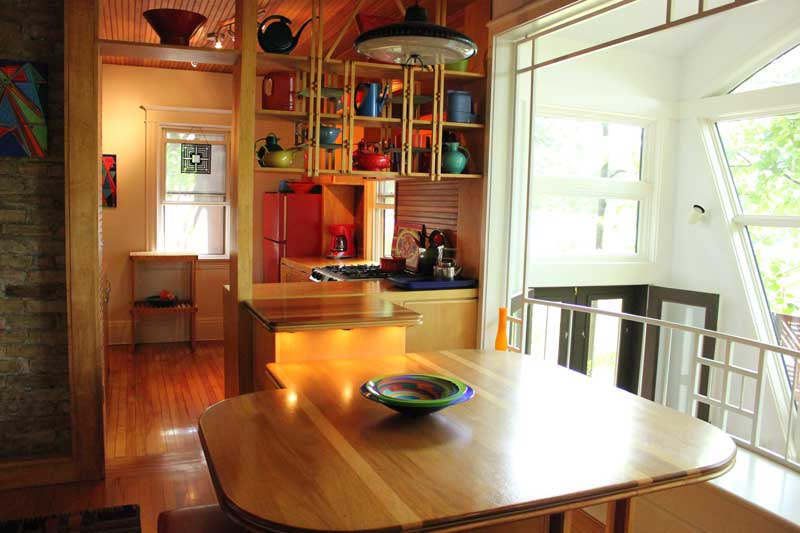 Upon buying their Thomas Avenue house in 1973, Kathryn and Daryl Hansen first remodeled the kitchen to create more counter space. Daryl designed furniture, including the dining room table, to use space as efficiently as possible. A passive solar addition is pictured at right. Photo by Michelle Bruch