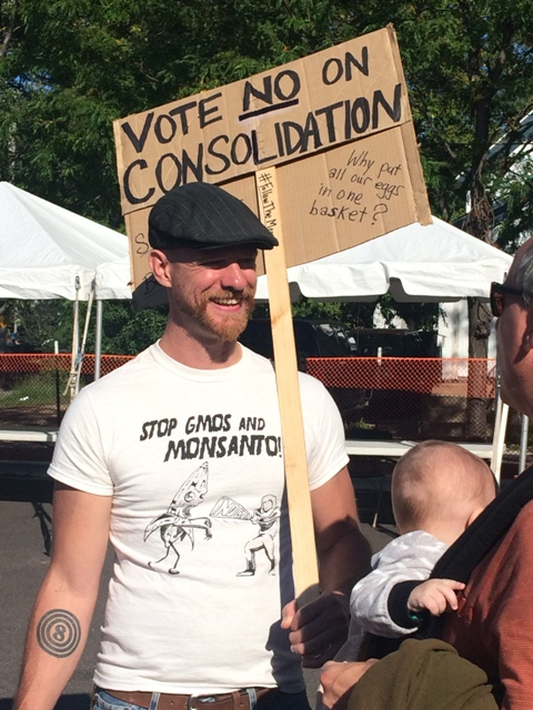 Wedge Co-op member Chris Loch pickets against consolidation. Photo by Michael Bayly