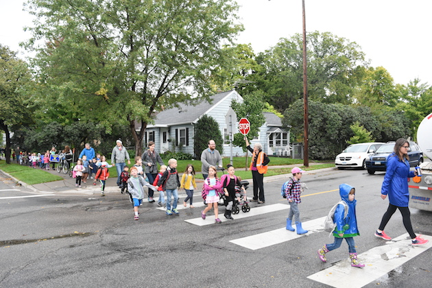 Malcolm Welter, 4, crosses the street in his pink hat and blue boots, nearing his school. Photo by Zoë Peterson.