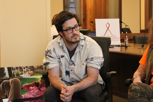 Jake Blair lost his brother Hunter, pictured in the photo behind him, to a heroin overdose.