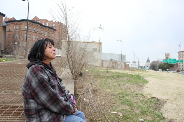 """Jane Bringsthem watches her friend panhandle from the median of the Hennepin/Lyndale corridor, not far from where she slept outside the night before. """"I can go home if I want to,"""" she says."""
