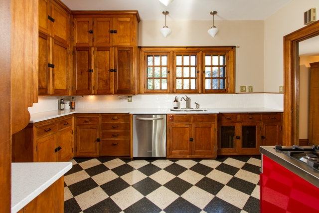 """New quartz counter tops, fresh neutral paint and new stainless appliances updated a vintage kitchen with the original 1920s cabinets. """"Kitchens are very important to buyers, so we often recommend a kitchen refresh such as this,"""" says Numrich. Photo by Seth Hannula"""