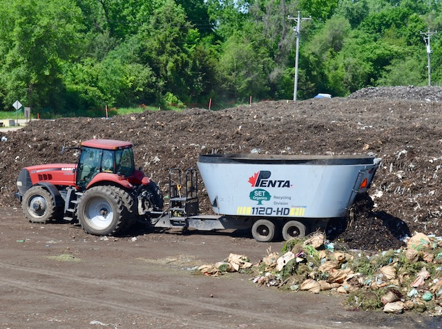A tractor spreads a mixture of yard waste and organic waste into a long pile called a windrow.
