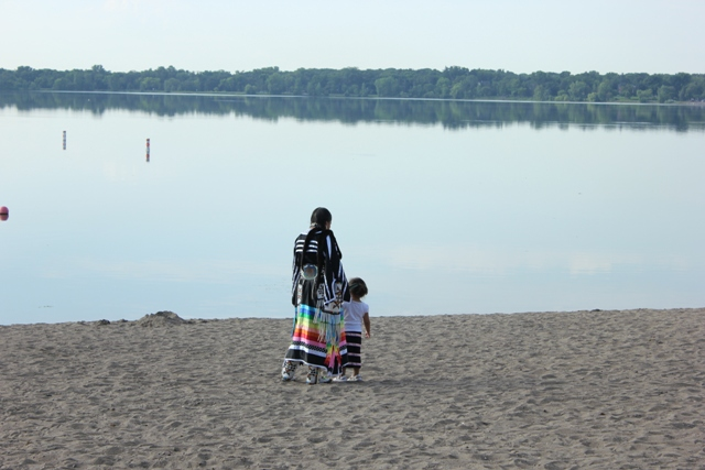 Ariel Waskewitch and daughter Nakoda Kootenay, visiting from Canada, pause at Bde Maka Ska (Lake Calhoun).