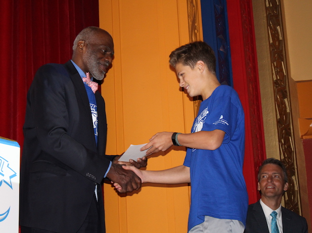 Page shakes hands during the assembly with a student who had perfect attendance the previous school year.