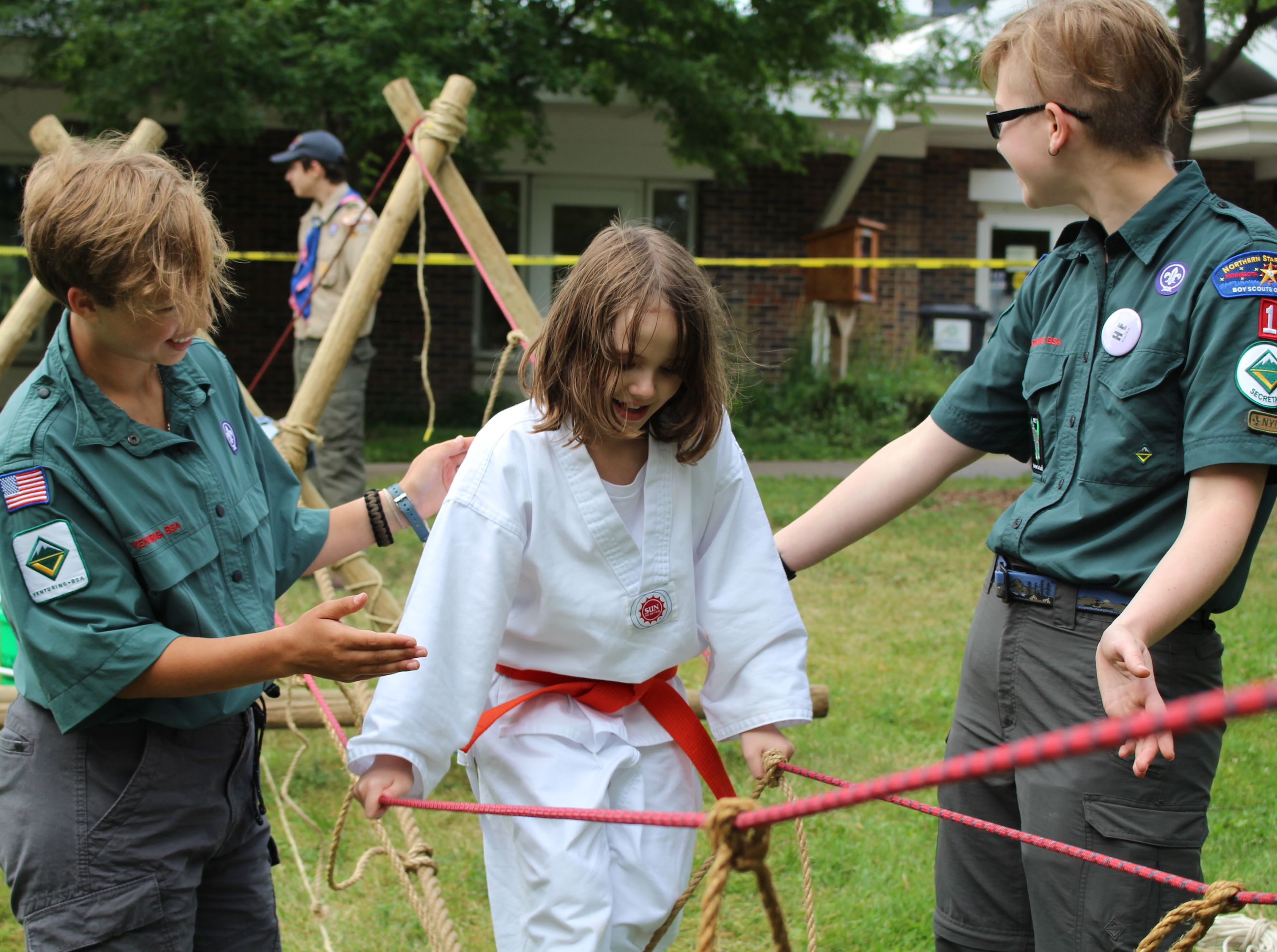 Victoria Johnson (left) and Beck Crain (right) of the Venturing program help Ruby Delaney cross an obstacle course at the festival.