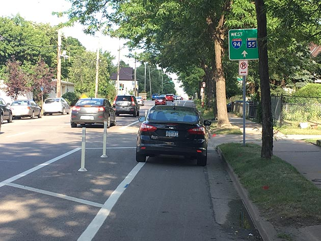 A car parked inside the protected bicycle lane on East 28th Street. Photo by Dylan Thomas