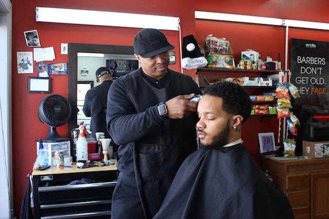 Fresh Cuts Barbershop owner Cameron Cook cuts Deron Howze's hair at 38th & 4th.