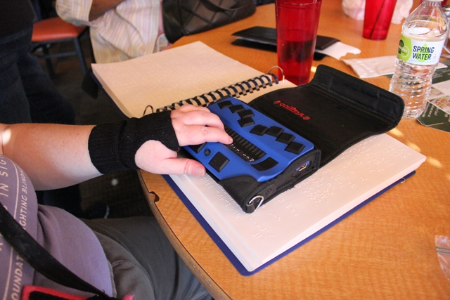 During lunch at Los Ocampo, one attendee reads a book in Braille and plays hangman on a refreshable Braille keyboard.
