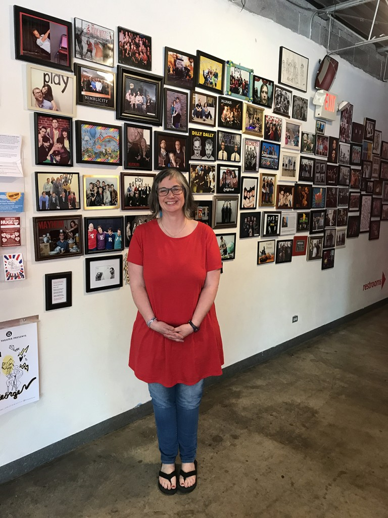 "HUGE co-founder Jill Bernard poses in front of a wall of photographs of improv troupes that have performed at the theater. ""Groups always ask how can they get our picture up here,"" she said. ""We say, 'You have to go to Target, print it, get a frame and put it up here. It's not a juried exhibition.'"" Photo by Zac Farber"