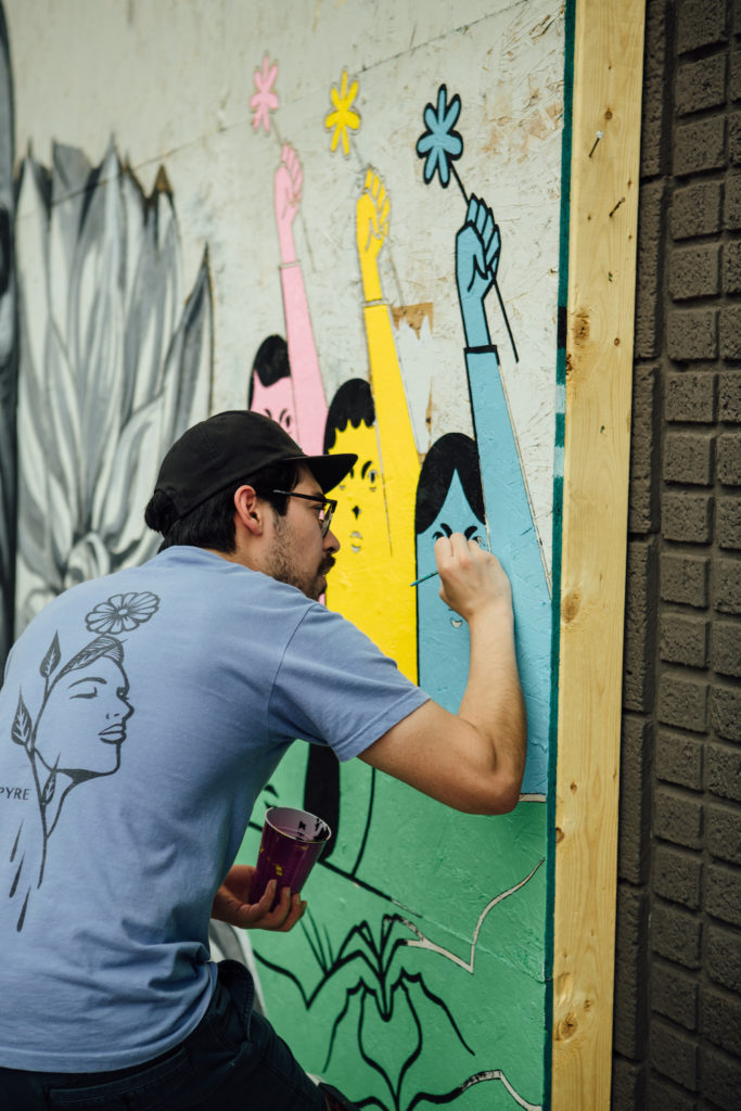 Jose Dominguez paints a storefront in the Wedge